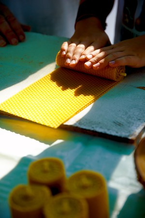 chandler: making candle from honey bee wax plate at market