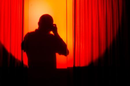 courtain: silhouette of photographer on orange courtain taking photos