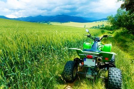 Quad verde en el paisaje en el camino en el campo. Foto de archivo
