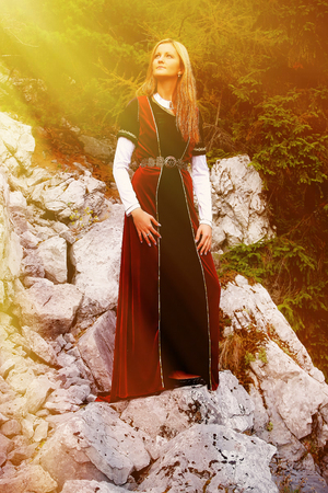 cultic: Beautiful young woman with blonde hair and a historical dress posing on a rock in mountain. Sunlight effect.