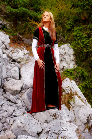 cultic: Beautiful young woman with blonde hair and a historical dress posing on a rock in mountain.