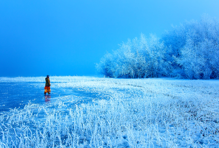 Woman on ice lake. Snowy landscape and snow covered trees and ice lake. Stock Photo