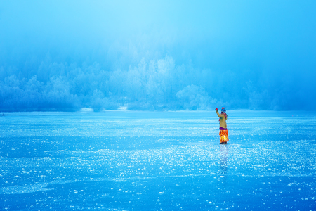 Woman on ice lake in beautiful ethno dress. Prayer for the lake. Stock Photo