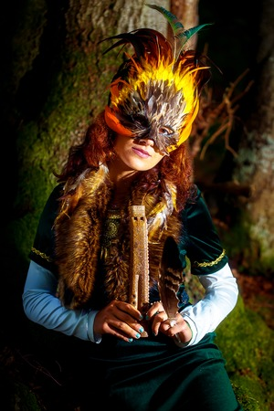 girl with shamanic feather mask and historic dress in woodland surroundings playing wooden ornamental flute.