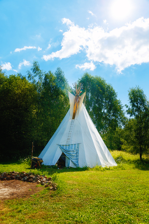 white teepee indian tent standing in beautiful summer landscape. Stock Photo