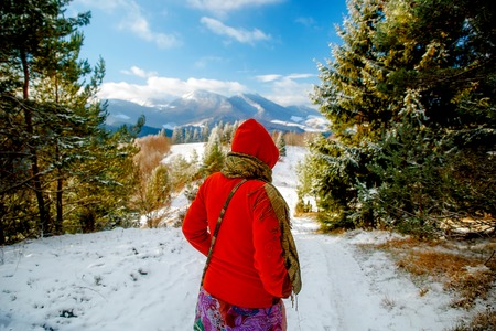 girl in colorful ethno dress standing amids winter landscape.