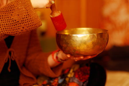 Spiritual girl immersed in meditative sounds of Tibetian bowl. Archivio Fotografico - 104653164