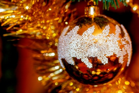 Close Up of Christmas-tree decorations. Golden color and blur background.