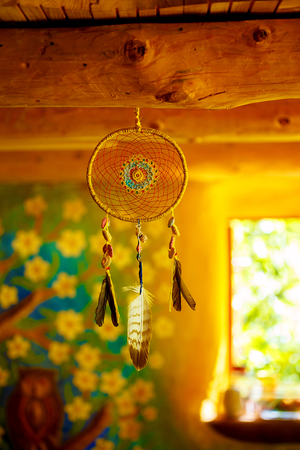 dream catcher with eagle and raven feathers in cosmic space.