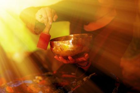 spiritual girl immersed in meditative sounds of tibetian bowl. Light efect.