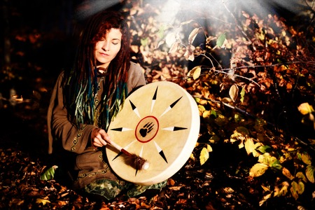 beautiful shamanic girl playing on shaman frame drum on background with leaves and flowers. Фото со стока