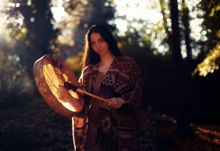 hermosa chica chamánica jugando en el tambor de marco de chamán en la naturaleza.