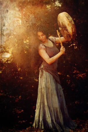 hermosa chica chamánica jugando en el tambor de marco de chamán en la naturaleza, efecto de foto antigua. Foto de archivo