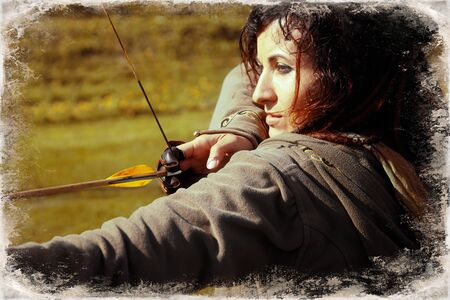 detail of a woman training shooting with a bow on a meadow, Archivio Fotografico