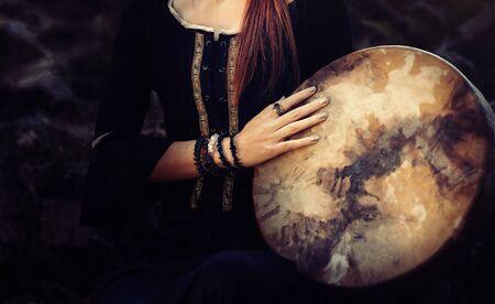 Hermosa niña chamánica jugando en el tambor de marco de chamán en la naturaleza