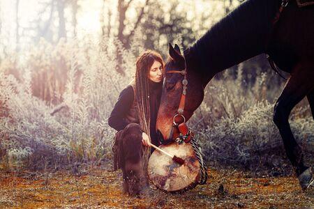 joven temida con su caballo y tambor de marco chamánico.