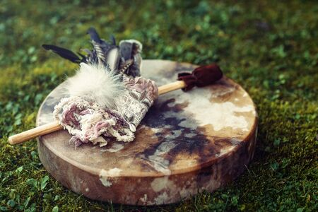 shamanic drum and shamanic feathers on denim Stock Photo