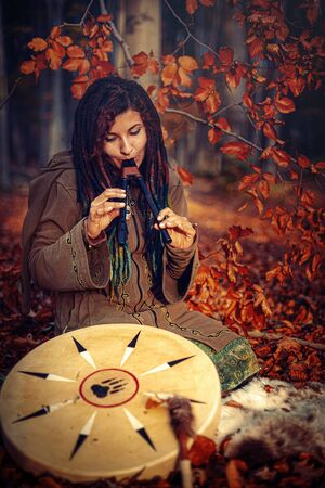 dreadlocks woman in forest, with double flute and shaman drum.