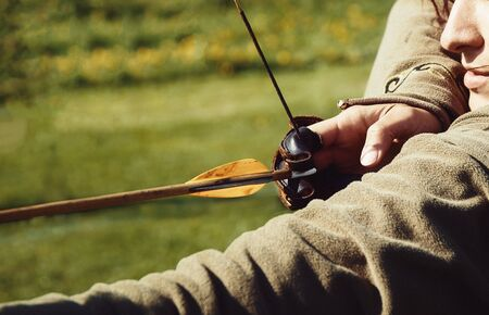 detail of a woman training shooting with a bow on a meadow, Banco de Imagens - 138258350