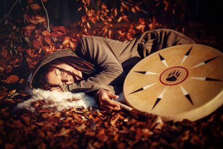 beautiful sleeping shamanic girl and shaman frame drum in the nature.