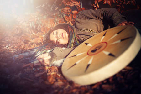 beautiful sleeping shamanic girl and shaman frame drum in the nature.