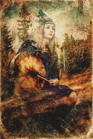 beautiful shamanic girl playing on shaman frame drum in the nature. Computer collage and painting effect. 写真素材