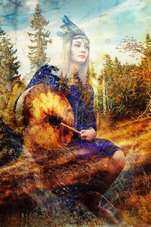 beautiful shamanic girl playing on shaman frame drum in the nature. Computer collage and painting effect. Stock Photo