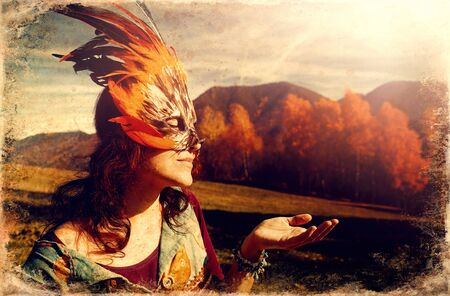 Young woman with a colorful feather face mask, old photo effect.