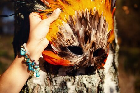 colorful feather face mask in woman hand