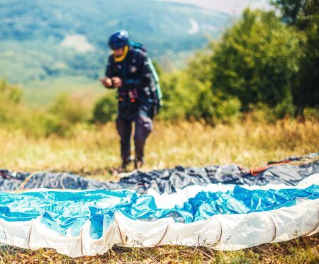 Paragliding in the mountains, paraglider on the ground