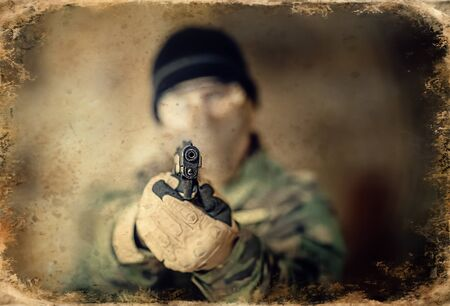 Airsoft soldier with a rifle, old photo effect