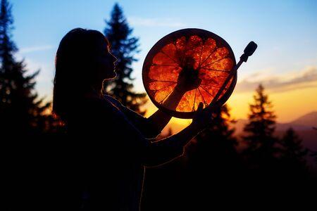 beautiful shamanic girl playing on shaman frame drum in the nature Stock Photo