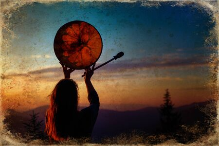 Shamanic girl playing on shaman frame drum in the nature, old photo effect