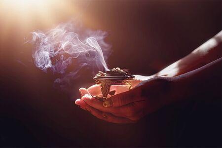 incense in a woman hand, incense smoke on a black background. Reklamní fotografie