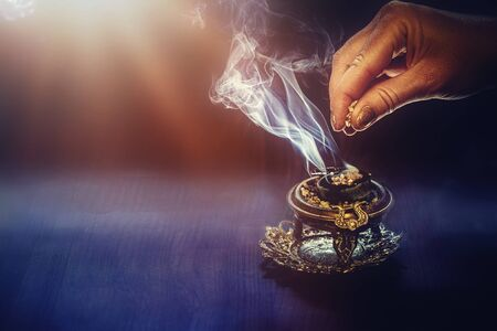 incense in a woman hand, incense smoke on a black background. Stock Photo