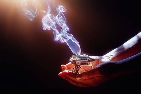 incense in a woman hand, incense smoke on a black background