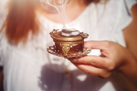incense in a woman hand, incense smoke on a blur background