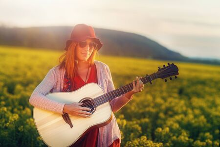 woman playing with guitar and blurred background.