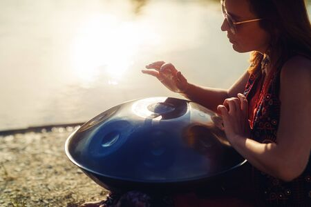beautiful woman playing with hangdrum in nature. Stock Photo