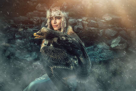 beautiful shamanic woman with eagle in the nature.