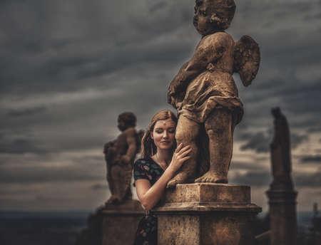 beautiful fashion model near an angel statue. Stock fotó