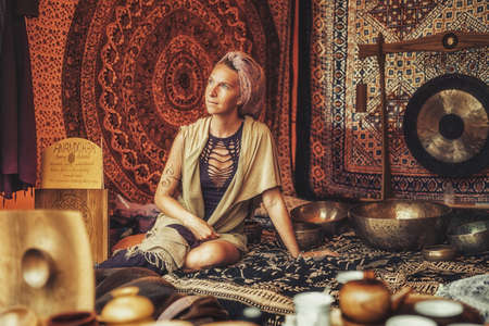 Spiritual girl immersed in meditative sounds of tibetian bowl.
