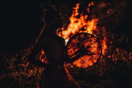beautiful shamanic girl playing on shaman frame drum in the nature. Imagens
