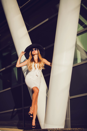 trendy girl in a white dress and sunglasses posing on the background city Stok Fotoğraf