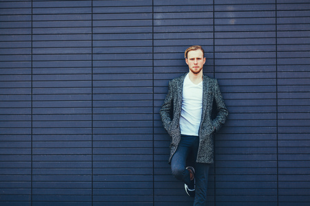 outerwear: handsome man posing in coat on blue background. copy space
