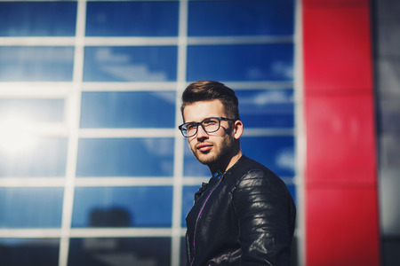 Confident handsome man in glasses and leather jacket. Men's beauty, fashion.