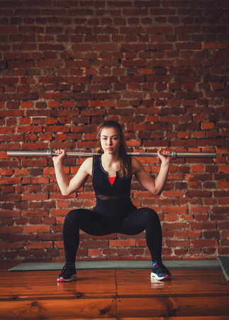 Sporty woman squats with barbell training