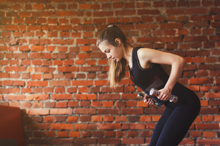 Sporty woman doing a workout with dumbbells at the gym. copy space