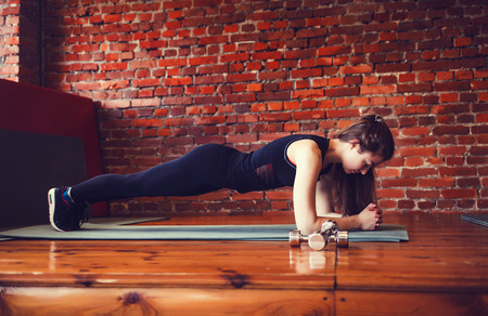 Young muscular woman doing core exercise on fitness mat in the gym.