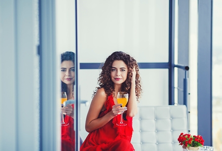 Young curly woman tasting fresh juice sitting on couch at balcony